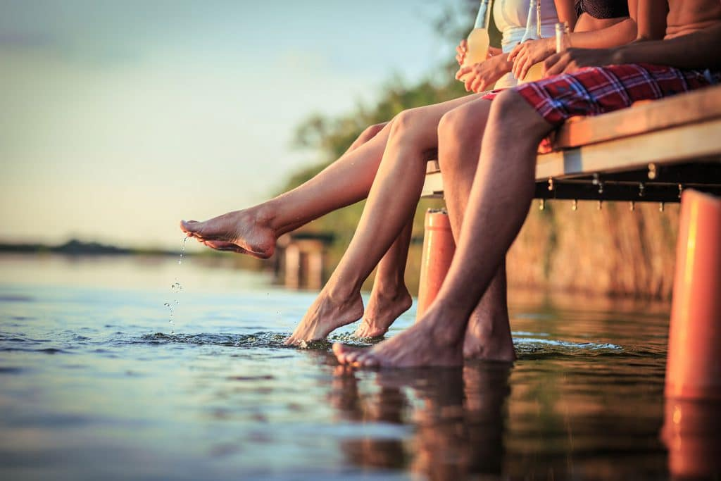 Shot of people's legs sitting on a dock with feet in water.