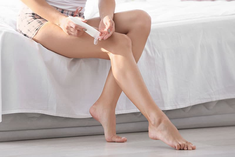 Woman's legs sitting on bed applying lotion